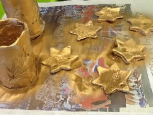 Spraying with gold paint the kids efforts at Christmas craft with the air dry clay