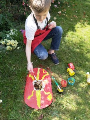 boy painting roman shield